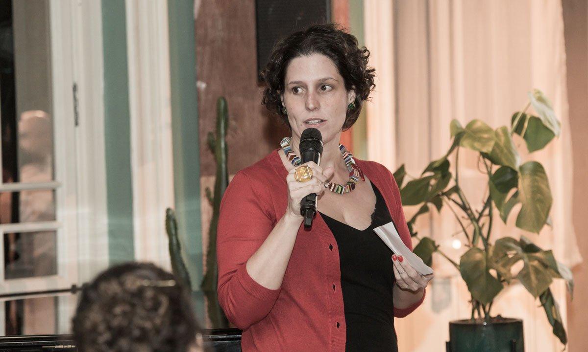 Na imagem, Luciana Zaffalon, mulher branca de cabelo castanho e curto, posa ao centro. Veste uma blusa preta com casaco vermelho e segura um microfone na mão direita. Em sua mão esquerda, um papel. Ela está numa sala, com paredes brancas, cinzas e verde. Ao fundo, duas plantas.